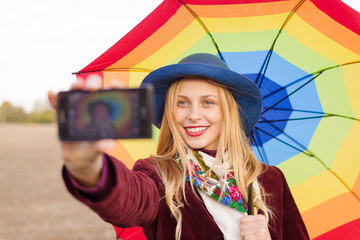 Beautiful young woman in hat holding umbrella and making selfie