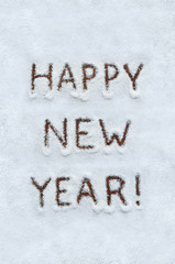 Text HAPPY NEW YEAR written on snow with wood background. Vertical holiday top view postcard.