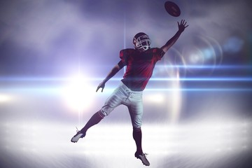 American football player trying to catch football ball