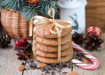 Spiced cookies with almonds. Christmas gifts. Round cookies, tied with ribbon and spruce branch in a basket on the table