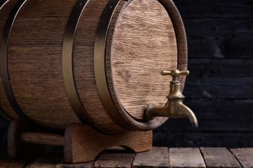 Old oak barrel on rack on grunge wooden table still life