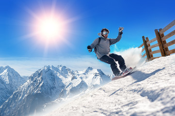 Snowboarder freerider / Snowboarder man holding snowboard in the air jumping with mountains on background