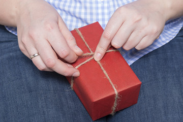 Female hands holding gift with twine