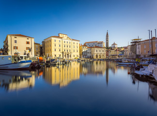 Venetian Port and The Main Square Tartini of Piran City Reflected on Water in Slovenia.