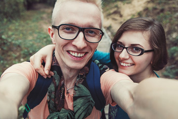 Cheerful couple in glasses makes selfe outdoors