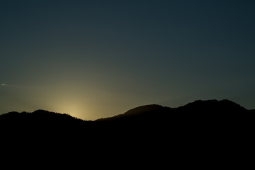 Dark Silhouette of Mountains on Yellow Sunrise Background.
