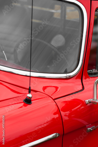 Close-up of car antenna of a red shiny classic vintage car