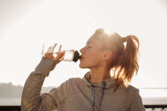 Young woman drinking water after cycling