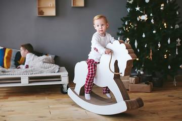 little boy riding a horse in a christmas interior