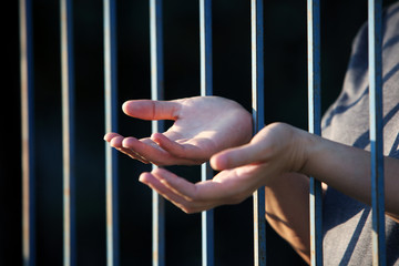 hand praying in jail