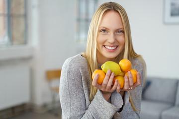 lachende junge frau hält zitronen und mandarinen in ihren händen