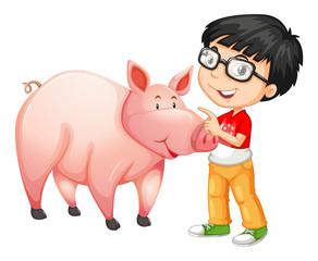 Little boy standing next to a pig