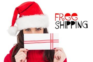 Composite image of festive brunette holding a gift