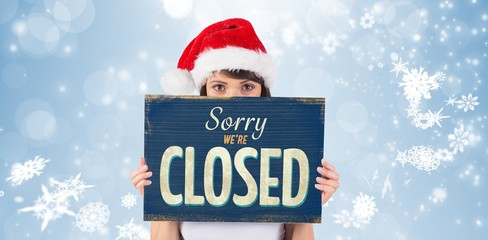 Composite image of pretty santa girl smiling at camera with sign