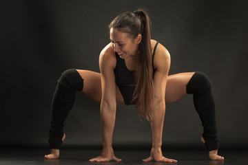 Muscular young woman athlete stretching on black