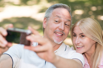 Mature couple taking a selfie in a park