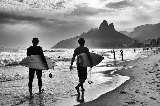 Scenic black and white view of Rio de Janeiro, Brazil with Brazilian surfers walking along the shore of Ipanema Beach