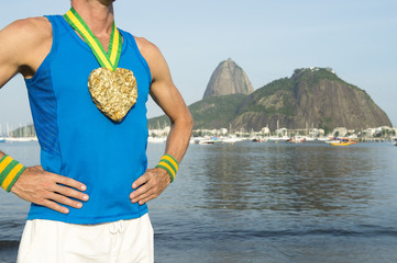 Athlete standing with gold medal in the shape of a heart at the Rio de Janeiro Brazil skyline at Botafogo