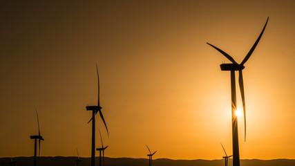 Siluetas de aerogeneradores en una puesta de sol
