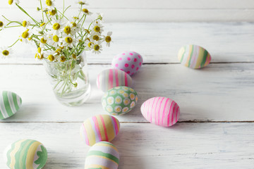 Bouquet of chamomiles in a glass vase and easter eggs in pastel