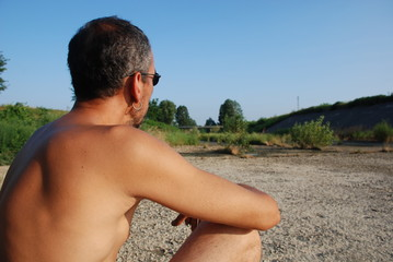 Man Sitting in Dried River Bed