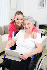 cheerful young girl teaching internet with computer tablet and sharing time with an old senior woman on wheelchair