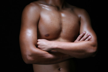 A hunky young asian male folding his hands with muscular chest
