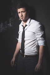 Young smoker with rolled up sleeves looking at camera