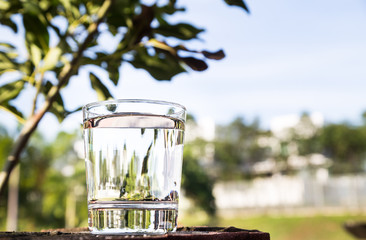 Refreshing water in transparent glass  against blue sky and greeneries