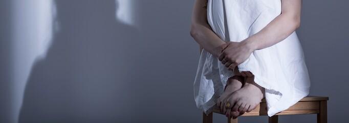Scared rape victim sitting curled