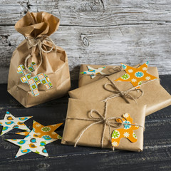 Christmas gifts in kraft paper with a homemade tag on a dark wooden surface. Vintage and rustic style