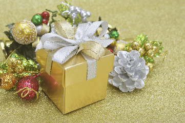 Gift box and christmas ornament on gold background