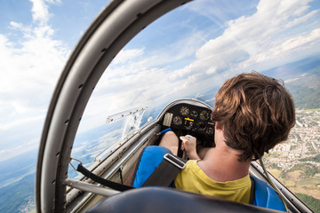pilot in the cockpit of the plane, glider gliding in the air over cities and countryside