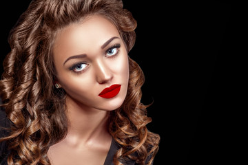 Beautiful Woman Model with Curls, Red Matte lips. Beauty face closeup. Isolated on Black Background. Long Shiny Curly Hair. Hairstyle..