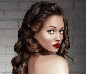 Beautiful Seductive Young Woman Model with Long Volume Curly Hair, Bronze Skin, Red Matte Sexy Lips, Blue Eyes and False Lashes. Trendy Evening Make up. Curls Hairstyle. Nude Shoulder..