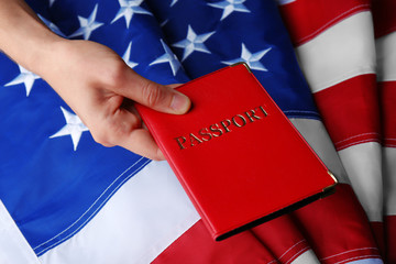 A hand holding the passport on American Flag background
