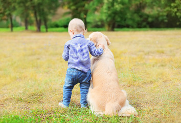 Little boy child and Golden Retriever dog together outdoors, bac