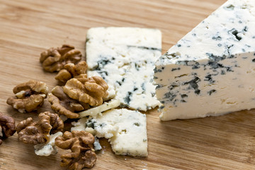 Dorblu Cheese with Walnuts on Wooden Background.