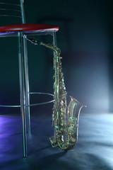Photo sur Aluminium Musique Beautiful golden saxophone near bar stool on a scene