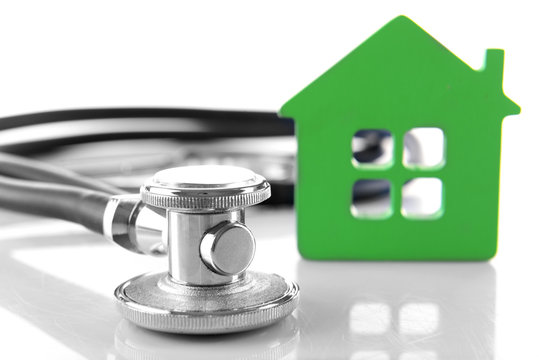 Concept of family medicine - green house and stethoscope isolated on white background