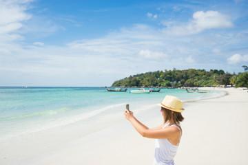 Female tourist taking photo of beautiful beach on smartphone.