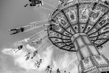 Traditional fairground ride on a sunny day, monochrome