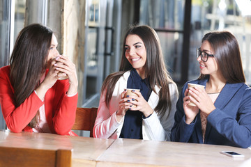 Attractive stylish girls pose with cup of coffee