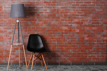 Black modern chair with lamp  on brick wall background