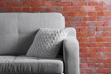 Comfortable sofa on brick wall background