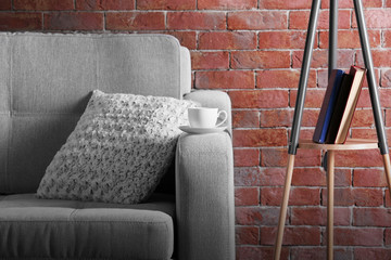 Comfortable sofa and lamp on brick wall background, close up