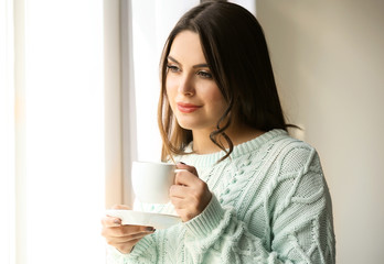 Woman standing near window in the room, close up
