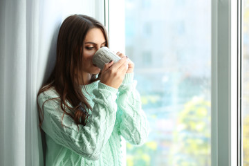 Woman drinking coffee near window in the room