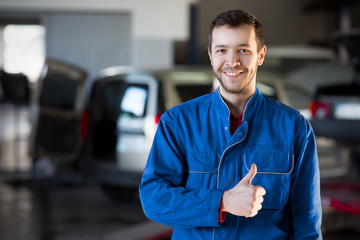 Auto repair service. Handsome smiling mechanic