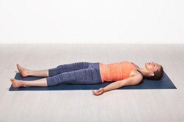 In de dag Ontspanning Sporty fit girl relaxes in yoga asana Savasana